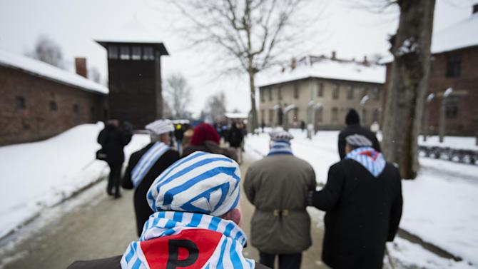 "Survivors walk past a watch tower after paying tribute to fallen comrades at the ""death wall"" execution spot in the former Auschwitz concentration camp"