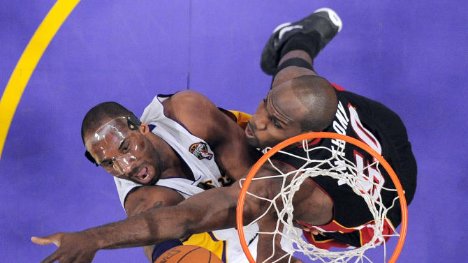 Los Angeles Lakers guard Kobe Bryant, left, shoots against Miami Heat center Joel Anthony during the first half of their NBA basketball game, Sunday, March 4, 2012, in Los Angeles. (AP Photo/Mark J. Terrill)