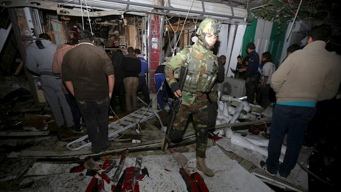 Iraqi security forces gather at the site of a car bomb in New Baghdad