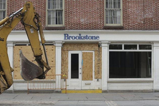 In this Thursday, Feb. 7, 2013 photo, a backhoe is driven past the shuttered Brookstone store on Fulton St. in New York. Nearly four months after Superstorm Sandy hit, the historic cobblestone streets near the water&#39;s edge in lower Manhattan are eerily deserted, and among local business owners, there is a pervasive sense that their plight has been ignored by the rest of Manhattan. (AP Photo/Mary Altaffer)