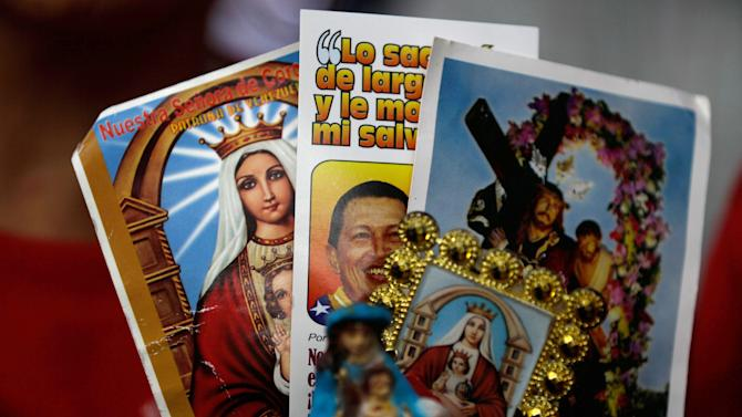 "A person holds up an image of Venezuela's President Hugo Chavez among religious images during a demonstration in support of him at the Simon Bolivar square in Caracas, Venezuela, Sunday Dec. 9, 2012. Chavez was heading back to Cuba on Sunday for more cancer surgery after announcing that the illness returned despite two previous operations, chemotherapy and radiation treatment.  Chavez said Saturday that if there are ""circumstances that prevent me from exercising the presidency further"" Vice-President Nicolas Maduro should replace him for the remainder of his term. (AP Photo/Fernando Llano)"