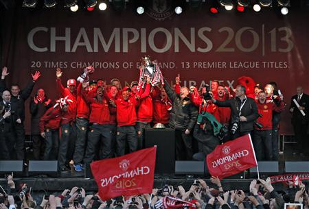 Manchester United players hold the English Premier League trophy with retiring manager Alex Ferguson after their victory parade at Albert Square in Manchester