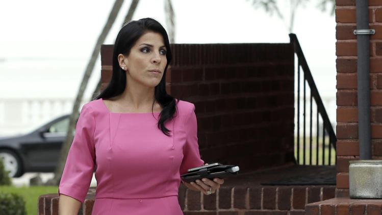 Jill Kelley leaves her home Tuesday, Nov 12, 2012 in Tampa, Fla. Kelley is identified as the woman who allegedly received harassing emails from Gen. David Petraeus' paramour, Paula Broadwell. She serves as an unpaid social liaison to MacDill Air Force Base in Tampa, where the military's Central Command and Special Operations Command are located. (AP Photo/Chris O'Meara)