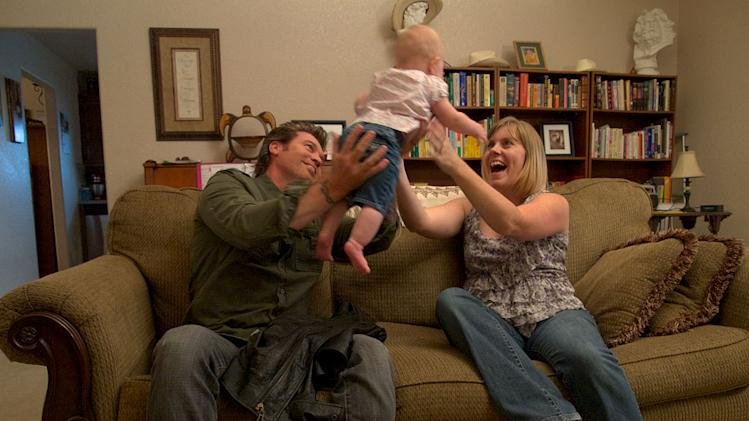 "Billy Ray Cyrus playing with Molly Rose (baby) and Katie Crabtree as seen on ""Surprise Homecoming."""