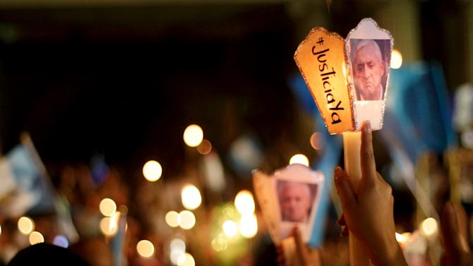 Demonstrators hold up candles with a picture of Guatemala's President Otto Perez Molina, during a protest demanding his resignation in Guatemala City