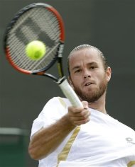 Xavier Malisse of Belgium returns a shot against Fernando Verdasco of Spain during a third round men's singles match at the All England Lawn Tennis Championships at Wimbledon, England, Friday, June 29, 2012. (AP Photo/Kirsty Wigglesworth)