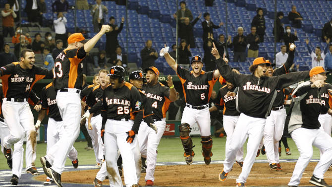 Netherlands' designated hitter Andruw Jones (25) scores a run on Kalian Sams' sacrifice fly as teammates celebrate their walk-off win over Cuba in their World Baseball Classic second round game at Tokyo Dome in Tokyo, Monday, March 11, 2013. Netherlands won 7-6 to advance to finals.(AP Photo/Koji Sasahara)