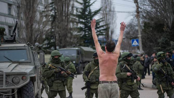 A Ukrainian man stands in protest in front of gunmen in unmarked uniforms as they stand guard in Balaklava, on the outskirts of Sevastopol, Ukraine, Saturday, March 1, 2014. An emblem on one of the vehicles and their number plates identify them as belonging to the Russian military. Ukrainian officials have accused Russia of sending new troops into Crimea, a strategic Russia-speaking region that hosts a major Russian navy base. The Kremlin hasn't responded to the accusations, but Russian lawmakers urged Putin to act to protect Russians in Crimea. (AP Photo/Andrew Lubimov)