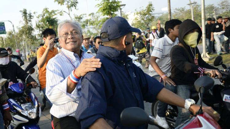 Protest leader Suthep Thaugsuban rides on the back of a motorcycle among anti-government protesters during a rally in Bangkok