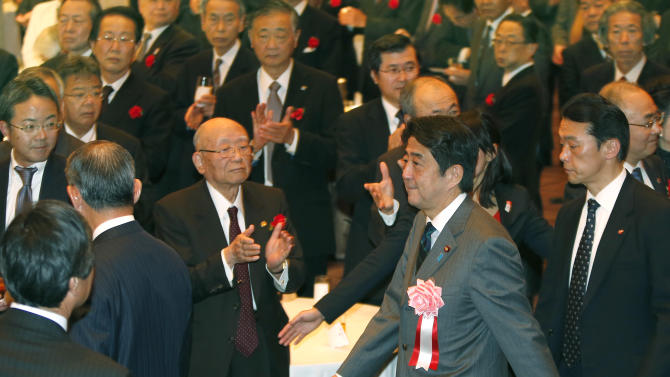 In this photo taken Monday, Jan. 7, 2013. Japanese Prime Minister Shinzo Abe, second from right, arrives for Japan's business organizations' joint New Year's party in Tokyo. Japan's ruling Liberal Democratic Party was in the final stages of drafting fresh stimulus spending Thursday, Jan. 10, reportedly totaling more than 20 trillion yen ($227 billion), rushing to fulfill campaign pledges to break the world's third-biggest economy out of its deflationary slump. Economy minister Akira Amari and Abe discussed details of the proposed stimulus package ahead of an announcement expected on Friday, officials said. (AP Photo/Shizuo Kambayashi)