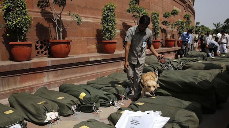 A sniffer dog inspects sacks containing copies of the 2014-15 union budget at the Indian parliament in New Delhi, Thursday, July 10, 2014. India's new government has introduced an ambitious reform-minded budget focusing on promoting manufacturing and infrastructure, raising the tax base and overhauling populist subsidies. (AP Photo/Manish Swarup)