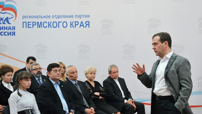 """Russian Prime Minister Dmitry Medvedev, right, meets with activists of the United Russia party in the city of Perm, about 1200 kilometers (750 miles) east of Moscow, Tuesday, Oct. 30, 2012. The sign reads, """"Perm regional branch of the United Russia party"""". (AP Photo/RIA-Novosti, Alexander Astafyev,  Government Press Service)"""