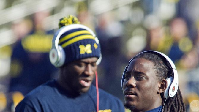 Michigan quarterback Denard Robinson, right, handles a ball alongside quarterback Devin Gardner, back, during warmups before an NCAA college football game against Iowa, Saturday, Nov. 17, 2012, in Ann Arbor, Mich. Robinson has missed the past two games with nerve damage in his elbow. (AP Photo/Tony Ding)