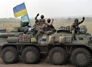 Ukrainian soldiers wave as they arrive near the eastern…