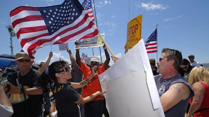 Demonstrators from opposing sides confront each other, Friday, July 4, 2014, outside a U.S. Border Patrol station in Murrieta, Calif. Demonstrators on both sides of the immigration debate had gathered where the agency was foiled earlier this week in an attempt to bus in and process some of the immigrants who have flooded the Texas border with Mexico. (AP Photo/Mark J. Terrill)
