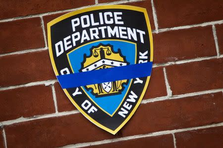 An NYPD logo is pictured on a wall above a makeshift memorial at the site where two police officers were shot in the head in the Brooklyn borough of New York