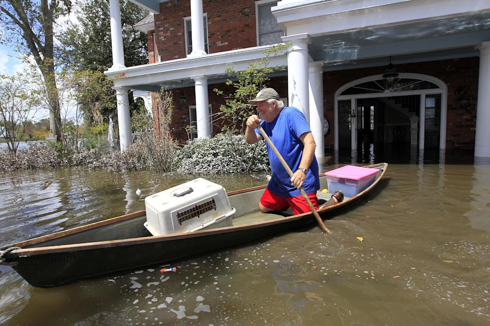 Don Duplantier paddles a pirogue from his flooded home as floodwaters from Hurricane Isaac recede in Braithwaite, La., Sunday, Sept. 2, 2012. Duplantier had retrieved his cat and had collected his daughter's bridesmaid dress for the upcoming wedding of his son. (AP Photo/Gerald Herbert)