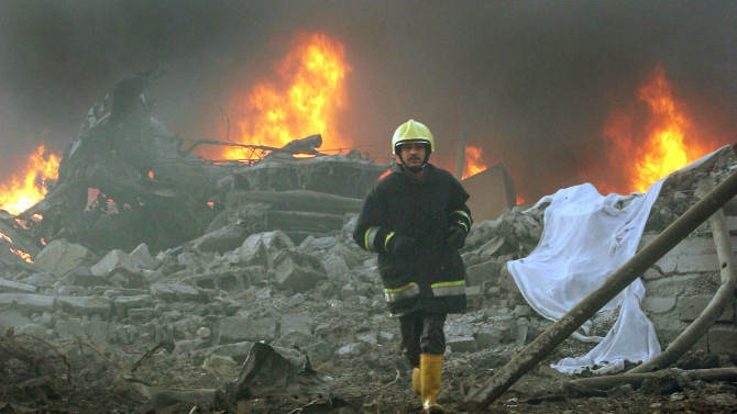 FILE - In a March 9, 2005 file photo a firefighter runs through the blast site after a garbage truck exploded near a hotel used by western contractors in central Baghdad, Iraq.  In the first tally of its kind, a federal investigative agency has calculated that at least 719 people, nearly half of them Americans, were killed working on projects to rebuild Iraq following the U.S. invasion in 2003.   (AP Photo/Hadi Mizban/file)