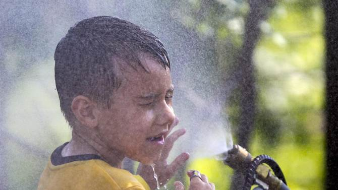 FILE - This July 6, 2012 file photo shows six-year-old Alexander Merrill of Sioux Falls, S.D., cooling off in a cloud of mist at the Henry Doorly Zoo in Omaha, Neb., as temperatures reached triple digits. Federal meteorologists say America was deep fried in 2012, becoming the hottest year on record by far. The National Climatic Data Center in Ashville, N.C., calculates that the average U.S. temperature in 2012 was 55.32 degrees Fahrenheit. That's a full degree warmer than the previous record of 1998. Normally, records are broken by about a tenth of a degree. (AP Photo/Nati Harnik, File)