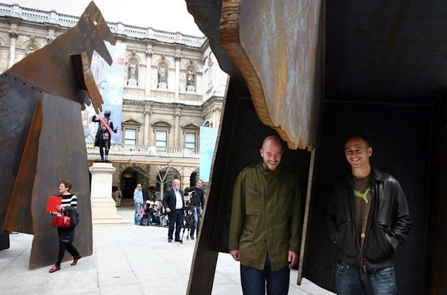 The Chapman brothers stand inside one of their sculptures at the Royal Academy of Arts in London, on June 6, 2007