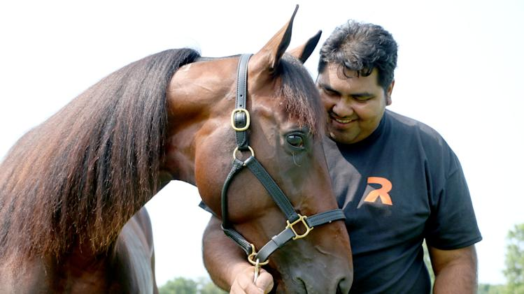 Caretaker Rufino Telon shares a playful moment with Hambletonian favorite Father Patrick after a morning workout at the Takter farm in East Windsor, New Jersey, Tuesday, July 29, 2014. Father Patrick is the 4-5 morning line favorite and will compete this Saturday, Aug. 2, in the $1 million Hambletonian race for 3-year-old trotters at the Meadowlands Racetrack in East Rutherford, New Jersey. (AP Photo/USTA Photo, Mark Hall)