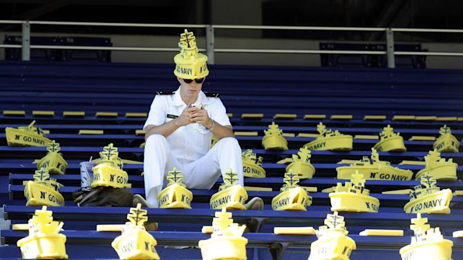 Midshipman Isaac Losee check his phone before the NCAA college football game between Navy and Air Force, Saturday, Oct. 5, 2013, in Annapolis, Md. (AP Photo/Nick Wass)