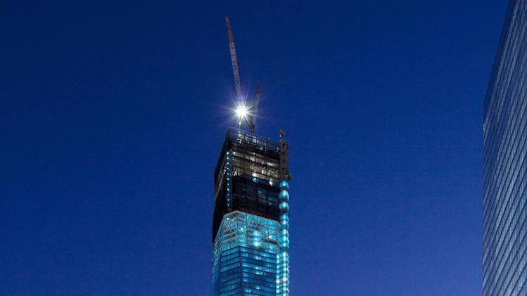 The tower known as 1 World Trade Center and the National September 11 Memorial, bottom, are bathed in light, Tuesday, Sept. 11, 2012 in New York. Tuesday is the eleventh anniversary of the terrorist attacks of Sept. 11, 2001. (AP Photo/Mark Lennihan)