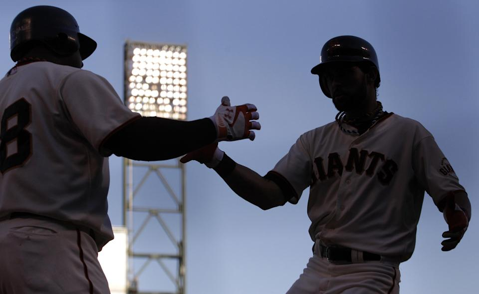 San Francisco Giants' Angel Pagan, right, is congratulated by Pablo Sandoval after Pagan hit a home run during the first inning of Game 2 of baseball's National League championship series against the St. Louis Cardinals Monday, Oct. 15, 2012, in San Francisco. (AP Photo/Ben Margot)