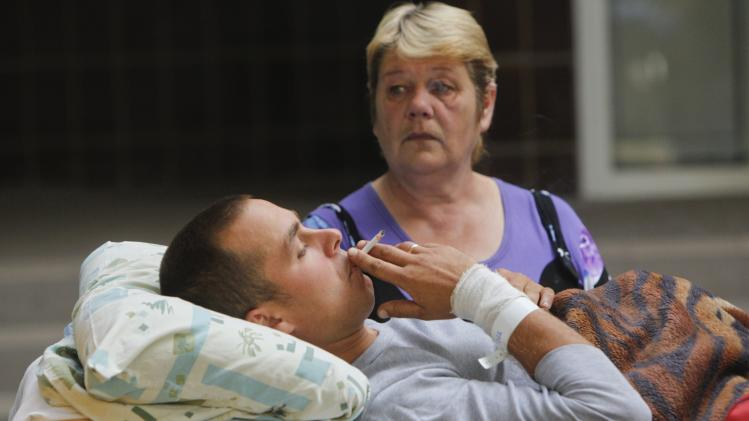 An injured Ukrainian serviceman smokes next to a relative before being put into ambulance for the transportation at a military hospital in Kiev