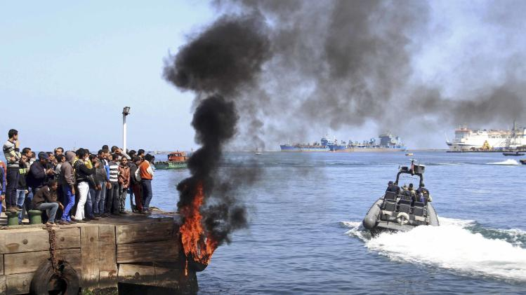 Several protesters set fire to tires on the city's dock in an attempt to prevent ships from coming in to the strategic city of Port Said at the Mediterranean end of the Suez Canal, in Egypt, Saturday, March 9, 2013. An Egyptian court on Saturday confirmed the death sentences against 21 people for taking part in a deadly 2012 soccer riot but acquitted seven police officials for their alleged role in a trial that has been the source of some of the worst unrest to hit Egypt in recent weeks. (AP Photo/Ahmed Ramadan)
