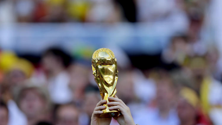 A spectator holds up a replica of the World Cup before the World Cup final soccer match between Germany and Argentina at the Maracana Stadium in Rio de Janeiro, Brazil, Sunday, July 13, 2014. (AP Photo/Matthias Schrader)