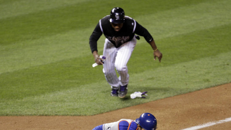 New York Mets catcher Mike Nickeas reaches for the ball as Colorado Rockies Jonathan Herrera runs to home plate on a double by Rockies batter Carlos Gonzalez in the fifth inning of their baseball game in Denver on Friday, April 27, 2012.  Herrera scored on the play. (AP Photo/Joe Mahoney)