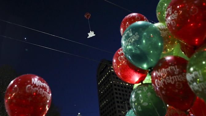 A sign hangs from balloons during a Black Lives Matter protest at a Christmas tree lighting ceremony on Black Friday in Seattle, Washington