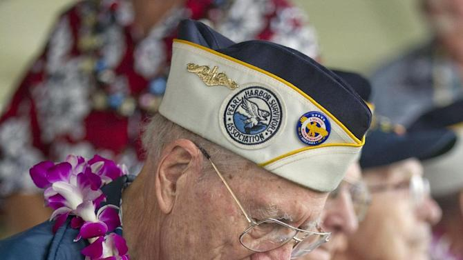 Pearl Harbor survivor Tom Berg, of Port Townsen, Wash., a sailor on the USS Tennessee, signs his autograph for an admirer Friday, Dec. 7, 2012, at Pearl Harbor, Hawaii. Many of the Pearl Harbor Veterans gathered at the World War II Valor In The Pacific National Monument remembering the 71th anniversary of the Dec. 7, 1941 Japanese surprise attack on Pearl Harbor in Honolulu. (AP Photo/Eugene Tanner)