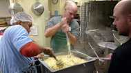 Volunteers mash potatoes for Christmas dinner at Siloam Mission on Monday.