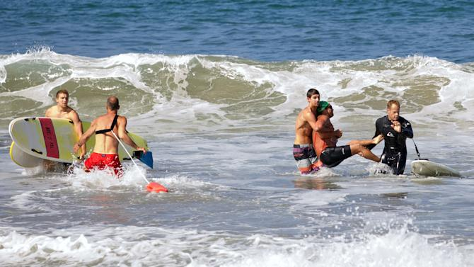 In this photo by Laura Joyce of goofyfootphotography.com, two men carry a swimmer, second from right, after he was bitten by a great white shark, as lifeguards close in at left in the ocean off Southern California's Manhattan Beach, Saturday, July 5, 2014. The man, who was with a group of long-distance swimmers when he swam into a fishing line, was bitten on a side of his rib cage according to Rick Flores, a Los Angeles County Fire Department spokesman. The man's injuries were not life-threatening and he was taken to a hospital conscious and breathing on his own, Flores said. (AP Photo/goofyfootphotography.com, Laura Joyce)