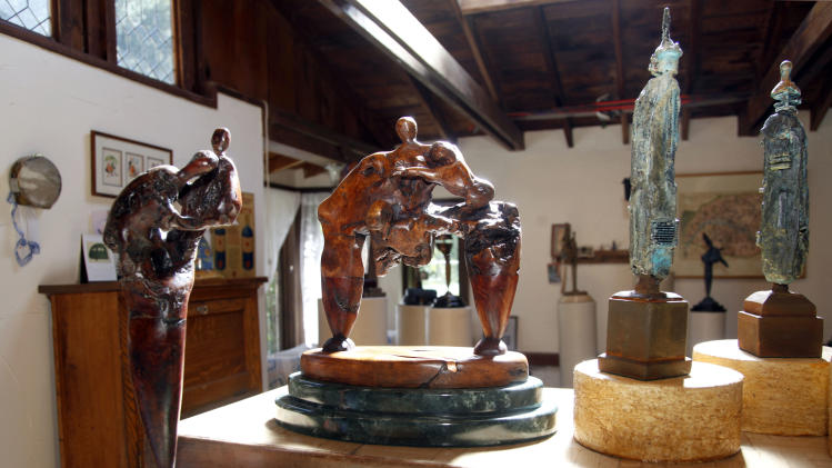 """In this Thursday, Sept. 18, 2012 photo, works by Tony Dow, actor, director and artist, from left, Two Figures and Struggle, are seen at his home and studio in the Topanga area of Los Angeles. When it comes time to sitting down in a studio and carving out bronze and wooden sculptures inspired by the nature all around him, Wally isn't leaving it up to the Beav these days. Dow, who famously played the Beaver's older brother Wally on the classic 1950s-60s sitcom """"Leave it To Beaver,"""" is carving out a name for himself in the art world these days, as an abstract artist. (AP Photo/Reed Saxon)"""