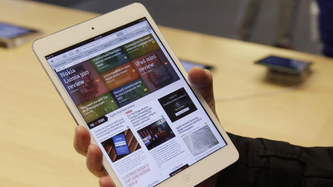 FILE -In this Friday, Nov. 2, 2012, file photo, a shopper check out the new Apple iPad mini at the Apple store on Michigan Ave.  in Chicago. The new iPad Mini is sure to please millions this holiday season. But fans of the latest full-size iPad have reason to look down on this newcomer: compared to other Apple products, the screen just isn't that good. (AP Photo/M. Spencer Green)