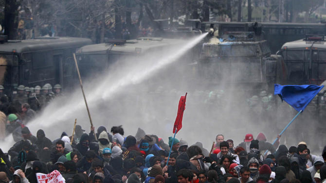Police spray water at demonstrators as they march towards La Moneda presidential palace on the second day of a national strike in Santiago, Chile, Thursday Aug. 25, 2011. Chileans marched peacefully Thursday, demanding profound changes in the country's heavily centralized and privatized form of government. Union members, students, government workers and Chile's center-left opposition parties joined the nationwide two-day strike. (AP Photo/Victor R. Caivano)