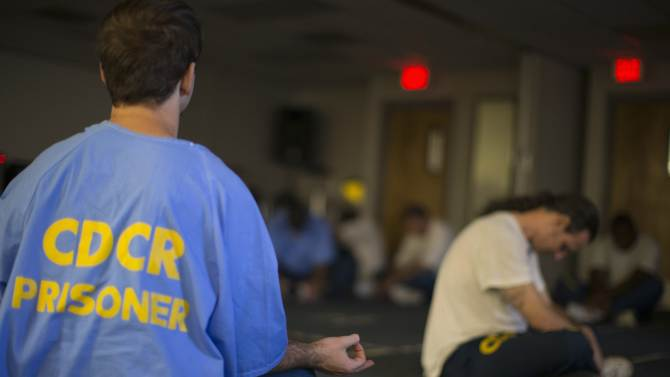 """Inmates meditate before the workshop """"Commedia Dell'Arte"""", part of the The Actors' Gang Prison Project program at the California Rehabilitation Center in Norco"""