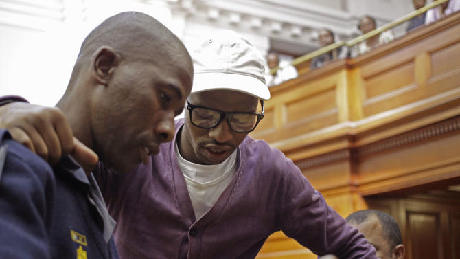 "Xolile Mngeni, center, arrives in court before being sentenced at Cape Town, South Africa, Wednesday, Dec. 5,  2012. A South African judge sentenced the triggerman in the 2010 honeymoon slaying of a Swedish bride to life in prison Wednesday, calling the shooter ""a merciless and evil person"" who deserved the maximum punishment for his crime. Prosecutors say the newlywed's British husband orchestrated the November 2010 killing. Judge Robert Henney did not hold back his contempt while sentencing Xolile Mngeni for the killing of 28-year-old Anni Dewani. Henney said that the shooter showed no remorse. (AP Photo/Schalk van Zuydam)"