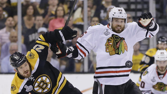 Boston Bruins defenseman Andrew Ference (21) and Chicago Blackhawks center Patrick Sharp (10) fight for position as the puck passes during the first period in Game 6 of the NHL hockey Stanley Cup Finals Monday, June 24, 2013 in Boston. (AP Photo/Elise Amendola)