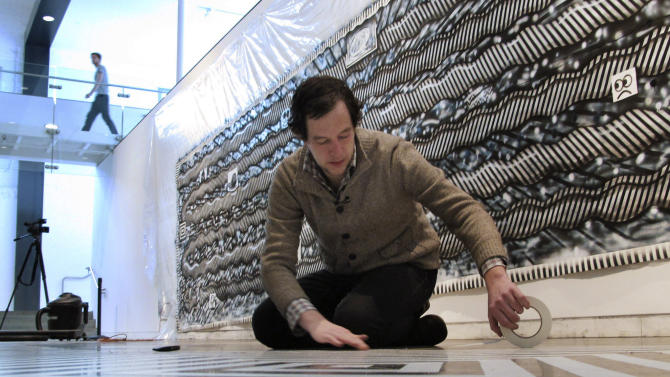 In this Tuesday, Feb. 19, 2013 photo, Ryan Travis Christian lays out a tape pattern on the floor in front of his wall-sized drawing at the Contemporary Art Museum in Raleigh, N.C. The Chicago artist completely reworked his wall-sized drawing several days into his first museum exhibition. (AP Photo/Allen Breed)