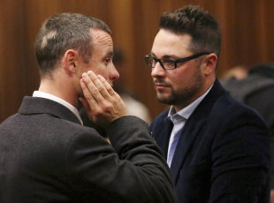 Oscar Pistorius speaks to his brother, Carl, in court. (AP)