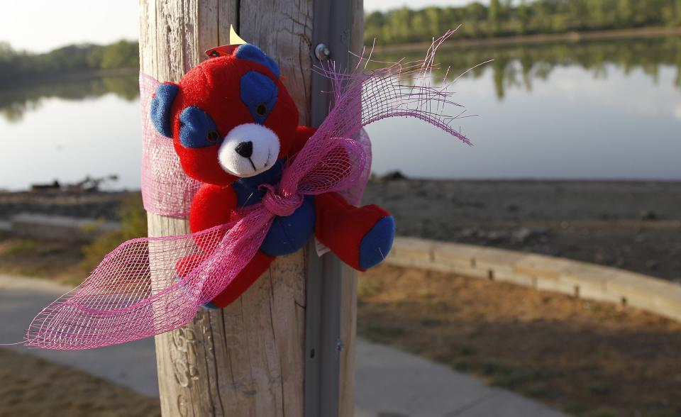 A bear is put up with ribbon at Meyers Lake as the search continues for Elizabeth Collins, 8, and her cousin Lyric Cook-Morrissey, 10, Wednesday, July 18, 2012, in Waterloo, Iowa. (AP Photo/Waterloo Courier, Matthew Putney)