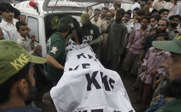 Pakistani rescue workers load a dead body into an ambulance after recovering from a burnt garment factory in Karachi, Pakistan on Wednesday, Sept. 12, 2012.