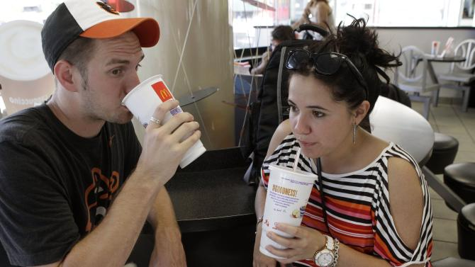 FILE - In this Sept. 13, 2012 photo, Luke Husemann, and Christina Nunez, of Baltimore, sip on extra-large soft drinks at a McDonald's restaurant in New York. The city defended its groundbreaking size limit on sugary drinks Wednesday, Jan. 23, 2013, as an imperfect but meaningful rein on obesity, while critics said it would hurt small and minority-owned businesses while doing little to help health. (AP Photo/Kathy Willens, File)