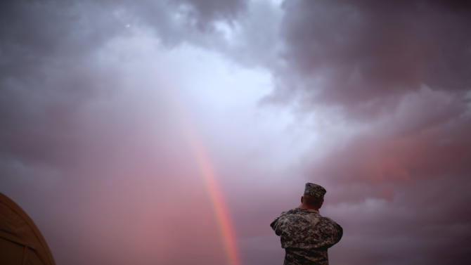 Spc. Christopher Aust, 25, of Harrison, Ark., with the U.S. Army's 4th Brigade Combat Team, 101st Airborne Division out of Fort Campbell, Ky., takes a picture of a rainbow at the Transit Center in Manas, Kyrgyzstan, while riding out a layover on the way home after completing a deployment in Afghanistan Wednesday, Aug. 10, 2011. The 4th Brigade Combat Team, 101st Airborne Division is returning home after a year in Afghanistan as the last brigade to deploy as part of President Obama's 30,000 troop surge. (AP Photo/David Goldman)
