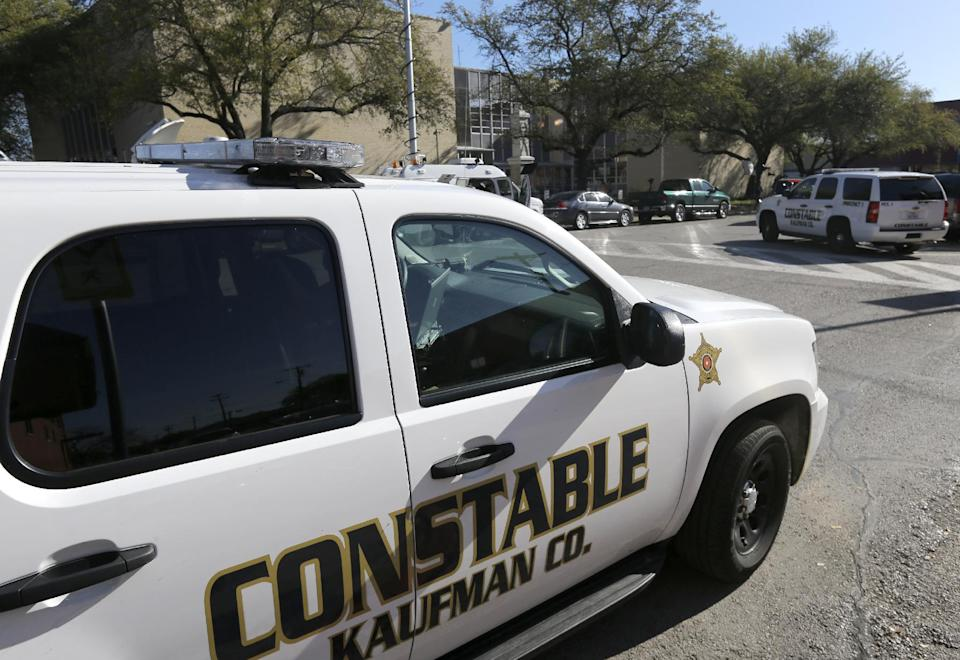 Kaufman county law enforcement vehicles are shown parked across the street from the county courthouse, rear, Monday, April 1, 2013, in Kaufman, Texas.   Law enforcement officials throughout Texas remained on high alert Monday seeking to better protect prosecutors and their staffs following the killing of county district attorney whose assistant was gunned down just months ago. (AP Photo/Tony Gutierrez)