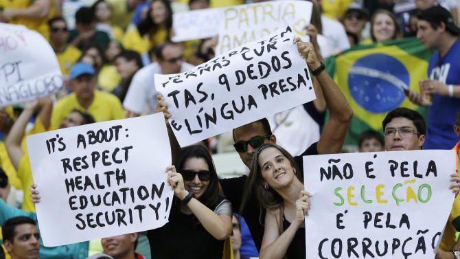 """Fans hold protest signs reading """"Not against the Brazilian team - against corruption"""" during the soccer Confederations Cup group A match between Brazil and Mexico at Castelao stadium in Fortaleza, Brazil, Wednesday, June 19, 2013. (AP Photo/Natacha Pisarenko)"""